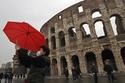 سائح يرتدي قناعاً واقياً ويلتقط صورة سيلفي على خلفية كولوسيوم في روما